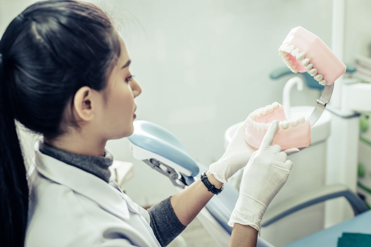 Female dentist explaining dental implants to patient in clinic